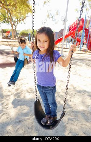 Jungen und Mädchen spielen auf Swing im Park