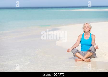 Ältere Frau meditieren am Strand - Stockfoto