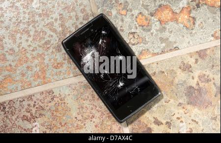 Smartphone auf harten Boden mit gebrochenen Bildschirm abgelegt. - Stockfoto