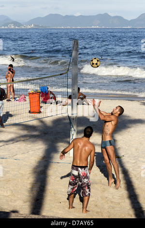 Spieler-Fußball (Fußball und Volleyball) im Schatten der Palme am Strand von Ipanema. Rio De Janeiro. - Stockfoto