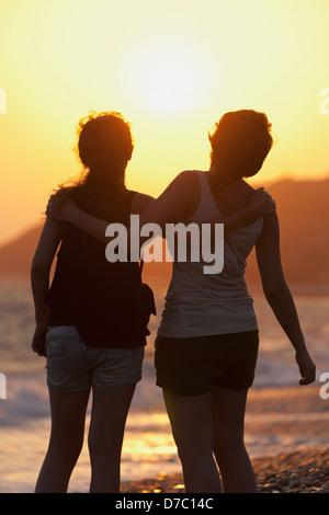 Zwei Freunde in einer Umarmung wie sie den Sonnenuntergang am Rand des Wassers; Aphrodite Bay Zypern - Stockfoto