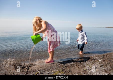 Junge Mädchen und ihr Bruder spielen am Strand von See Ontario, Kanada - Stockfoto