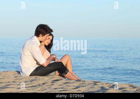 Paar, umarmen, sitzen auf dem Sand des Strandes vor das Meer - Stockfoto