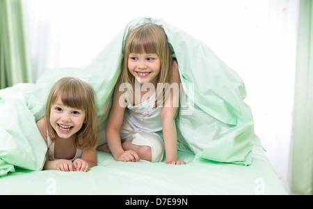 Zwei kleine Mädchen, die unter Decke auf dem Bett liegend - Stockfoto