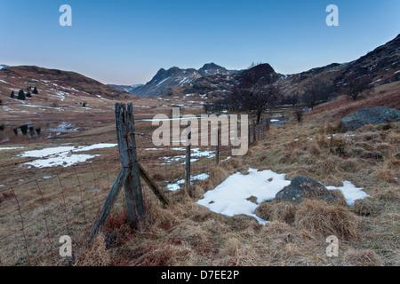 Blea Tarn Stacheldraht Maschendrahtzaun mit einer Aussicht auf die saisonabhängige in den frühen Morgenstunden. - Stockfoto