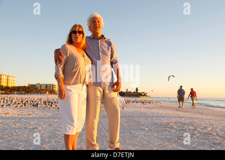 Barfuß älteres Paar, ein Spaziergang entlang des Strandes den Sonnenuntergang genießen - Stockfoto