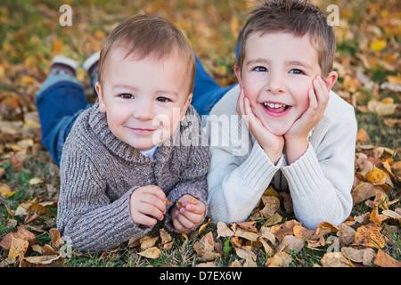 Porträt von zwei jungen, die Verlegung auf dem Boden im Herbst Laub; St. Albert Alberta Kanada - Stockfoto