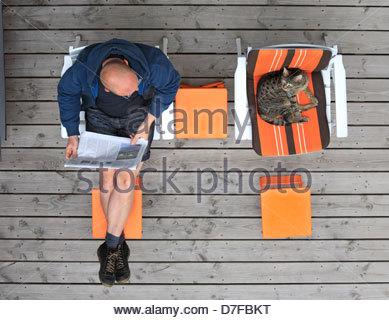 Erhöhte Ansicht von einem reifen Mann liest eine Zeitung mit einer Katze auf der Promenade, Bonn, Deutschland - Stockfoto