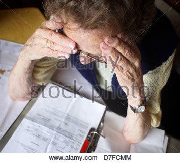 Ältere Frau arrangieren Papiere in einem Ringbuch und Leiden mit Kopfschmerzen - Stockfoto