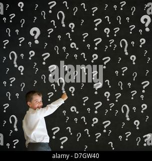 Schreiben junge verkleidete sich als Geschäftsmann mit Fragen Kreidestriche auf Tafel Hintergrund - Stockfoto