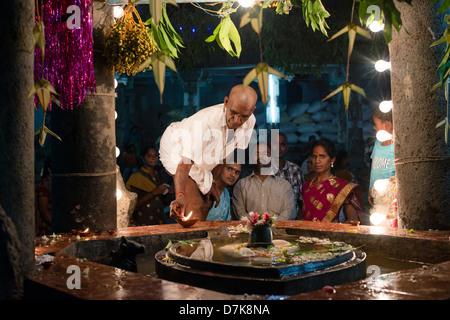 Ein Pilger leuchtet eine Öllampe auf den Zahntempel in Kandy, Sri ...