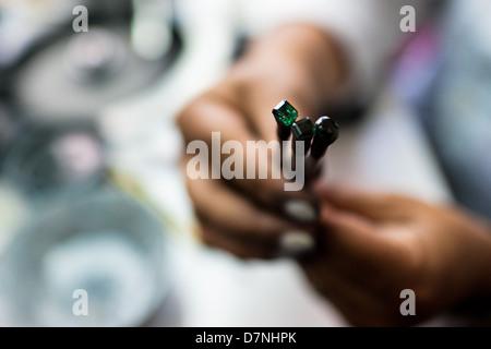 Ein Smaragd Fräser zeigt einem Edelstein, sie schneiden und Polieren-Workshop in Bogota, Kolumbien arbeitet. - Stockfoto