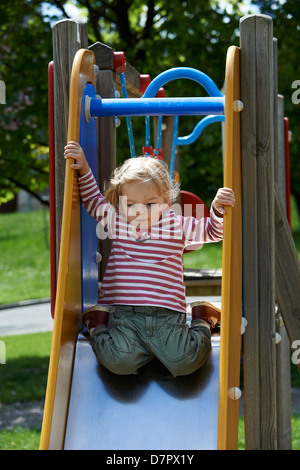 Blonde Mädchen Kind gleitende Folie auf einem Spielplatz - Stockfoto
