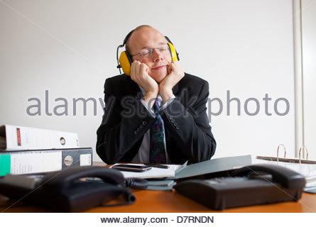 Geschäftsmann, tragen von Gehörschutz und Tagtraeume in einem Büro - Stockfoto