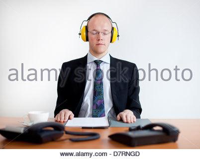 Geschäftsmann, tragen von Gehörschutz und meditieren in einem Büro - Stockfoto
