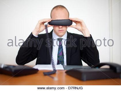 Kaufmann für seine Augen mit einem Telefonhörer - Stockfoto