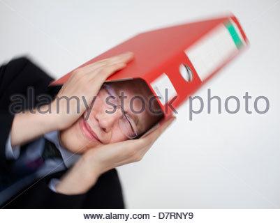 Kaufmann betont einen Ordner über den Kopf halten und auf der Suche - Stockfoto