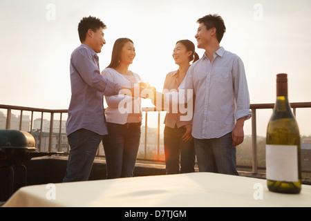 Gruppe von Freunden Toasten einander auf der Dachterrasse bei Sonnenuntergang - Stockfoto