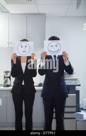 Geschäftsleute, die glückliche Gesichter auf dem Papier Holding - Stockfoto