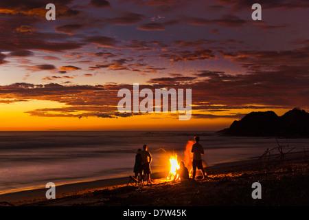 Menschen mit Treibholz Feuer bei Sonnenuntergang am Strand von Playa Guiones, Nosara, Nicoya Halbinsel, Provinz - Stockfoto