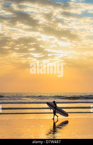 Surfer mit langes Brett bei Sonnenuntergang am beliebten Playa Guiones Surf Beach, Nosara, Nicoya Halbinsel, Provinz - Stockfoto