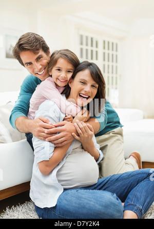 Familie umarmt im Wohnzimmer - Stockfoto