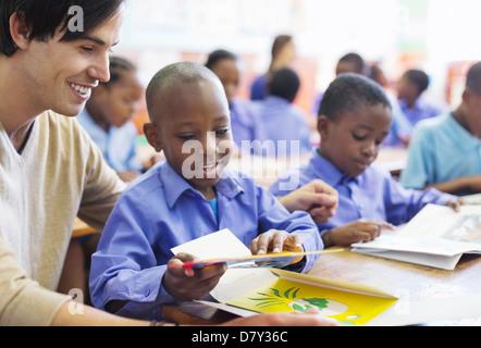 Lehrer mit Schüler im Klassenzimmer - Stockfoto