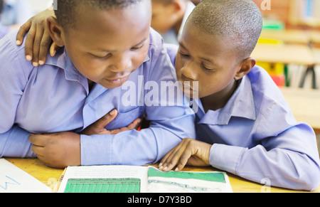 Studenten, die gemeinsam in der Klasse lesen - Stockfoto