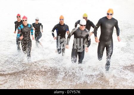 Triathleten in Neoprenanzüge in Wellen laufen - Stockfoto