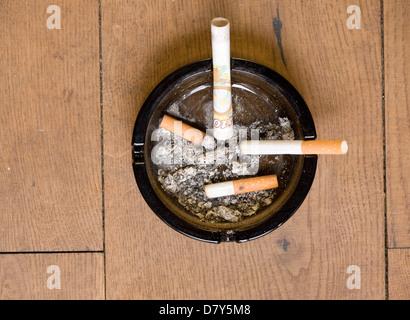 Zigaretten und zehn-Pfund-Note in einem Aschenbecher - Stockfoto