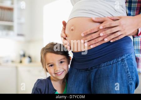 Mädchen lächelnd mit Bauch der schwangeren Mutter - Stockfoto
