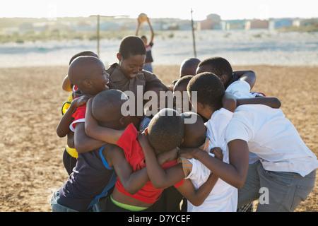 Jungen zusammengekauert auf Schmutz-Gebiet - Stockfoto