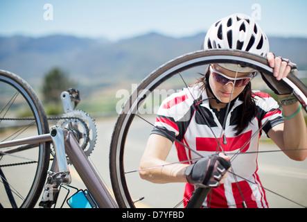 Radfahrer, die Anpassung der Reifen auf Landstraße - Stockfoto