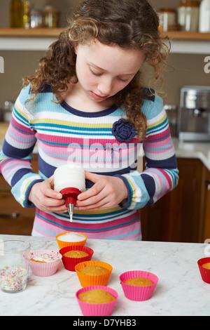 Mädchen dekorieren Cupcakes in Küche - Stockfoto