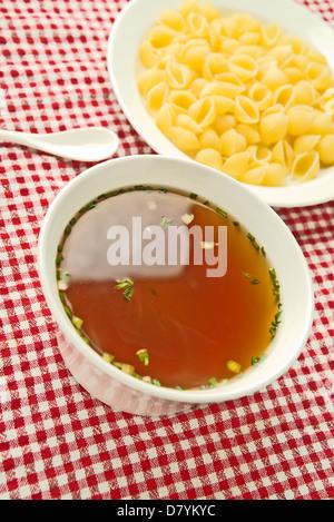 Gemüsesuppe, serviert auf einem Küchentisch für Essen mit rohen Nudeln in eine Schüssel. - Stockfoto