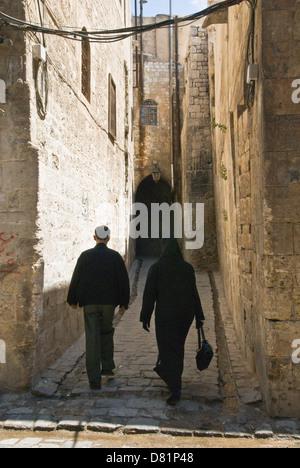 Aleppo Syrien. Ein Mann und eine Frau zu Fuß hinunter eine alte gepflasterte Gasse in der Altstadt, ein UNESCO-Weltkulturerbe. - Stockfoto