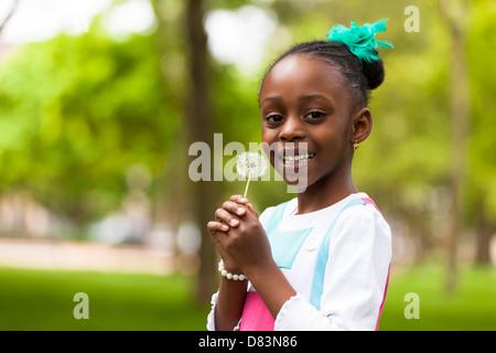 Outdoor-Porträt von einem netten junge schwarze Mädchen, die eine Löwenzahn Blume - Menschen in Afrika - Stockfoto