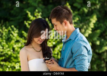 Horizontale Foto eines jungen Erwachsenen Mannes schlägt vor, seine Dame zeigt ihr einen Verlobungsring mit ihrem - Stockfoto