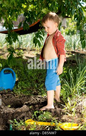 Kleiner Junge spielt im Garten stehen vor einem neu ausgehobenen Loch, umgeben von einem Kunststoff Schaufel und - Stockfoto