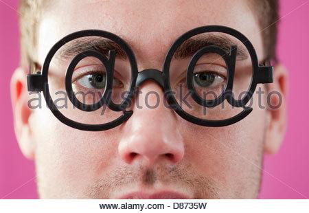 Nahaufnahme eines jungen Mannes tragen Brillen des At-Zeichens - Stockfoto
