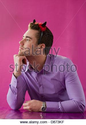 Junger Mann mit Teufelshörnern und denken - Stockfoto