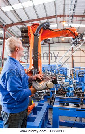Arbeiter, die Steuerung der Roboter Maschinen heben Stahl Fechten auf Produktionslinie im Werk - Stockfoto