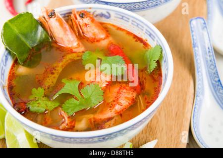 Tom Yum Goong - Thai klar scharf-saure Suppe mit König Garnelen und Austernpilzen mit Limettenscheiben serviert. - Stockfoto