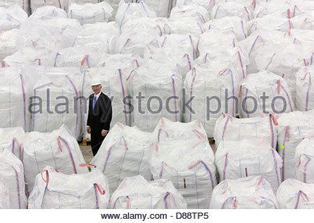 Porträt des Kaufmanns stehen unter großen Taschen von recyceltem Kunststoff-Pellets im Lager - Stockfoto