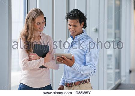 Unternehmer und Unternehmerin mit Kopfhörer sprechen und mit digital-Tablette in der Nähe von Fenster - Stockfoto