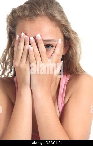 Schöne blonde Teenager Mädchen spähen das Auge durch ihre Hände auf einem weißen Hintergrund isoliert - Stockfoto