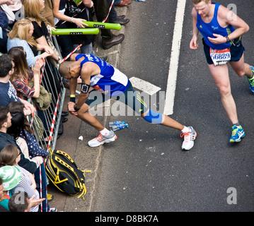 Läufer Athlet Konkurrent anhalten, um die Beine im Jahr 2013 London Marathon England Europa - Stockfoto