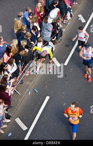 Läufer Konkurrent Athlet anhalten, um die Beine im Jahr 2013 London Marathon Victoria Embankment England Europa - Stockfoto