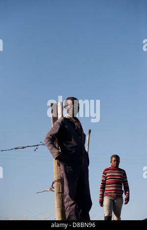Einem afrikanischen Mann gegen einen Weidezaun. - Stockfoto