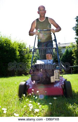 Reifer Mann mäht Rasen mit dem Rasenmäher - Stockfoto